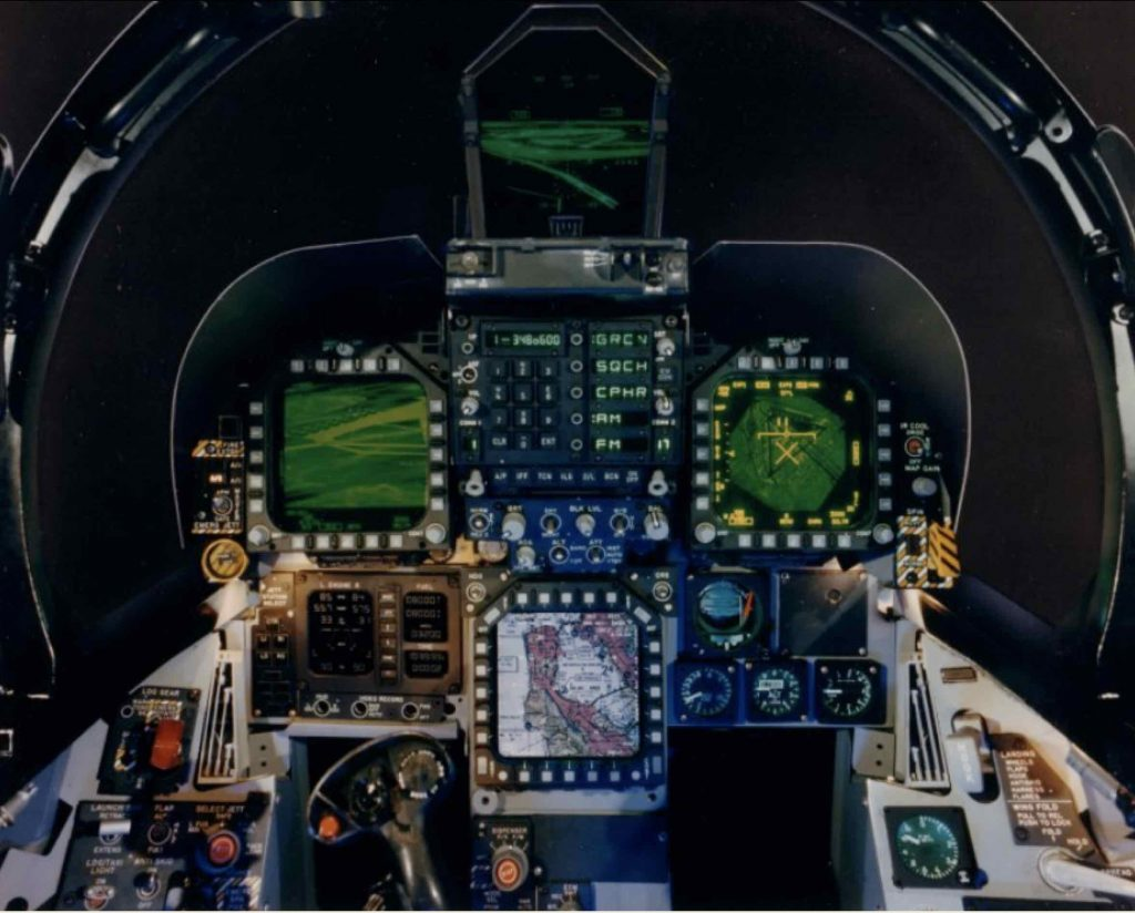 A photo of an aircraft cockpit with lots of small controls, and green and red lights